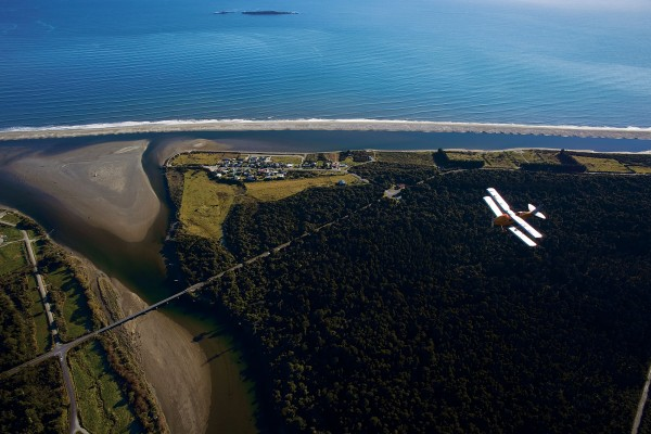 When Bert Mercer's Air Travel opened for business in 1934, West Coast settlements—such as Okuru, just south of Haast, pictured—were isolated islands cut off from each other by fierce rivers. The construction of bridges and the opening of the West Coast thoroughfare in 1965 spelt the end of the fixed-wing air services.