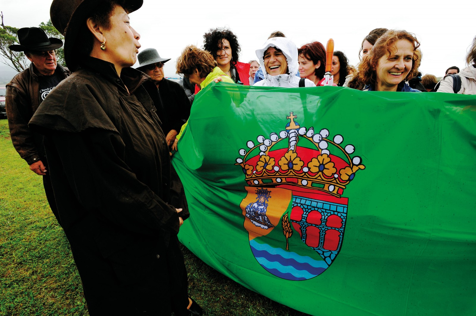 In step with the Maori tradition of introducing yourself with the landmarks of your hometown, Spanish relatives stand behind the green Segovian flag representing the city's Roman aqueduct and river.
