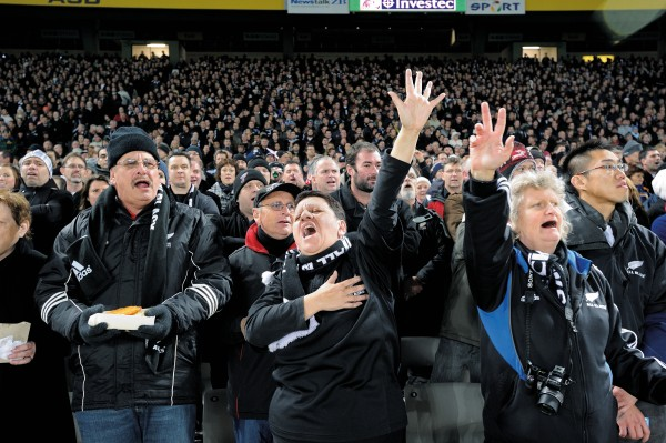 Fans dressed against the late evening chill at Eden Park launch enthusiastically into a rendition of the national anthem.