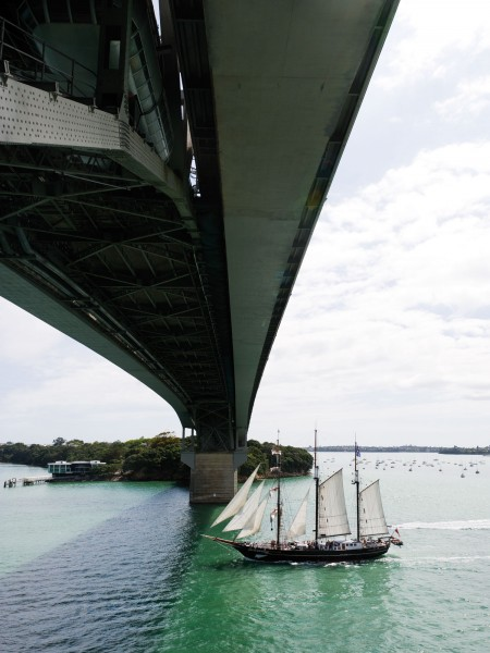 The sail-training barquentine Spirit of New Zealand passes under the Auckland Harbour Bridge. It is a modern vessel built with modern technology but exemplifies the type of vessel that brought the first British settlers and Governor Hobson to found the town of Auckland in 1840, inspiring the Anniversary Day Regatta.