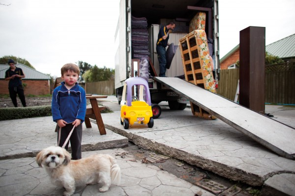 The McGlashon family were hoping their new home would be built before they had to leave their red-zoned neighbourhood in Burwood, but a city-wide backlog in consents and building made this impossible. Now one of the last residents in the street, three-year-old Lucas McGlashon watches on as his family's belongings are packed up for a temporary move to Kaiapoi. Like many children of the quakes, he has never known stable ground nor concrete without cracks.