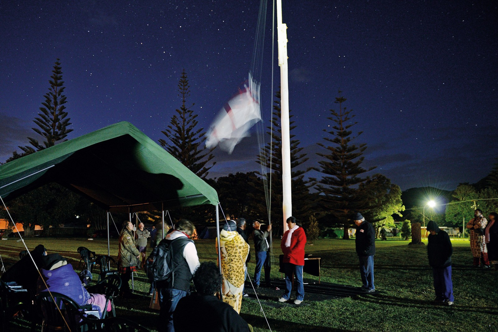 The flag of the Confederation of United Tribes ascends the flagpole at Te Tii marae, Waitangi, before dawn on October 28, 2013—'Independence Day', to Ngapuhi, because it marks their ancestors' assertion of rangatiratanga (sovereign authority) in 1835. The flag, chosen by Ngapuhi chiefs in 1834 and known as Te Kara (the colour), has enjoyed a renaissance in recent years as the Maori sovereignty movement has gained political ground. There are even small adhesive versions available for car windows.