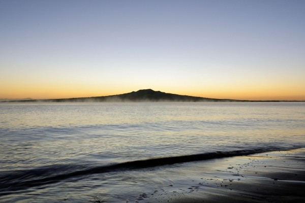 "Rangitoto, wrote Ferdinand von Hochstetter in his 1864 Geologie von New-Seeland, ""is for Auckland Harbour what Vesuvius is for the Bay of Naples, the 'symbol' of Auckland"". He described Rangitoto as small compared to the world's more renowned shield volcanoes, but nevertheless ""a true model of a volcanic mountain cone"". Seen here both softened by an early morning sea mist, and sharpened by the light of dawn, Rangitoto remains an enigma. It sits proudly offshore, and its exceptional symmetry affirms Auckland's identity. Yet its size and eruptive history are exceptional too, and serve as a warning. Another Rangitoto in the wrong place could threaten the city's population, infrastructure and identity."
