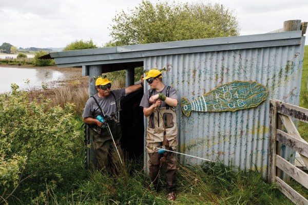 Allan Metcalfe and Philipp Loest mug for the camera outside 'The Koi Club', in masks and comedy hats bought to celebrate the World Koi Carp Classic. The tin shed was once the home base of koi bowfishing, until Metcalfe sold the surrounding farm. Now its windows are broken and the paint is peeling, but the records and legends of the World Koi Carp Classic remain legible on the walls.