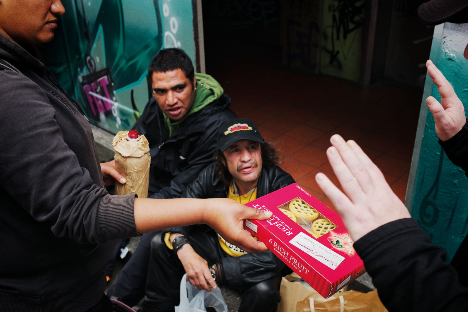 Many people experiencing homelessness have to manage on $50 or less a week after bills, and to make ends meet they often rely on food parcels provided by charities. Here, items of food are being handed out after a Wellington charity Christmas barbeque.
