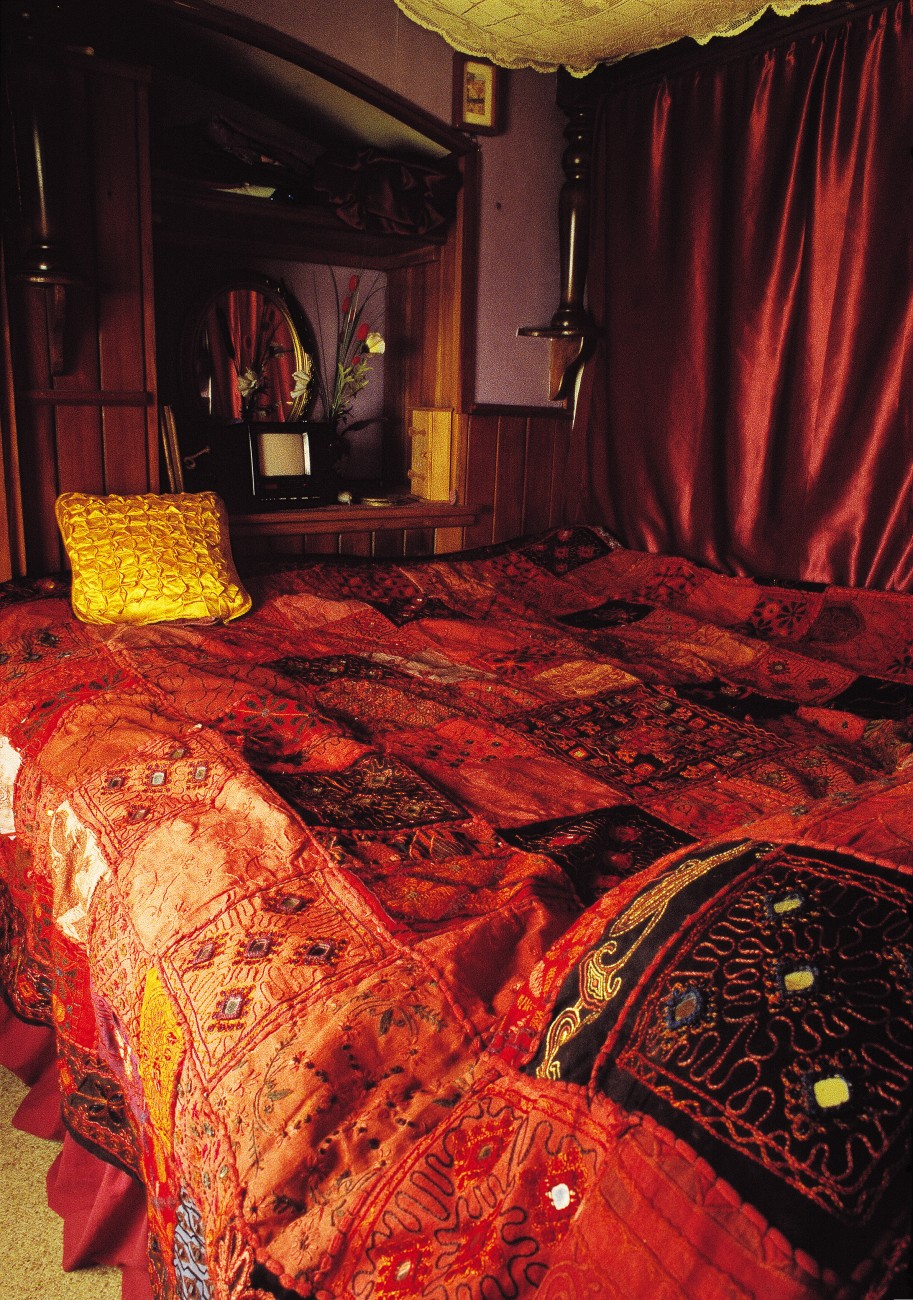 The Romains' master bedroom is proof that life on the road need not exclude a little luxury. The quilt, hand embroidered and studded with mirrors, come from Rajasthan, while the bedposts, in keeping with the house-trucker's recycling ethos, are fashioned from old table legs.