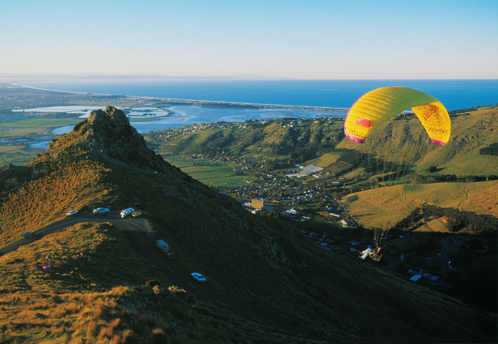 Borne aloft by updrafts close to Castle Rock, one of many crags in the Port Hills popular with climbers, a paraglider savours evening tranquillity and sweeping views towards the estuary of the Avon and Heathcote Rivers, near the Christchurch suburb of Mount Pleasant. The Summit Road—the backbone of a network of roads, biking tracks and walking trails linking a patchwork of bush reserves—is a boon to all who enjoy the outdoors. It provides easy access from both sides of the Port Hills to places of interest and adventure, catering for the geologist, historian and naturalist as well as trampers, cyclists and adrenalin junkies.