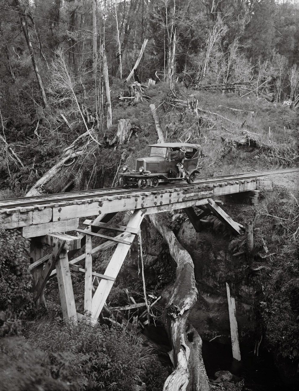 "In the pioneering years of motoring, cars were pressed into various forms of service—jacked up and with a belt run from a wheel to spin the saw at a timber mill, or adapted to become a ""rail car"" running on tramlines, as seen here. At least mud wasn't an issue once your car was on rails."