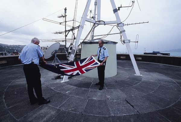 "Pat Magee (left) and Dan Matata fold the flag that flutters by day over the Beehive. To minimise entanglements in the capital's windy conditions, the flag comes in three sizes, known as the ""tablecloth,"" ""teatowel"" and ""handkerchief."" During raising and lowering, protocol dictates that the flag must never touch the ground."