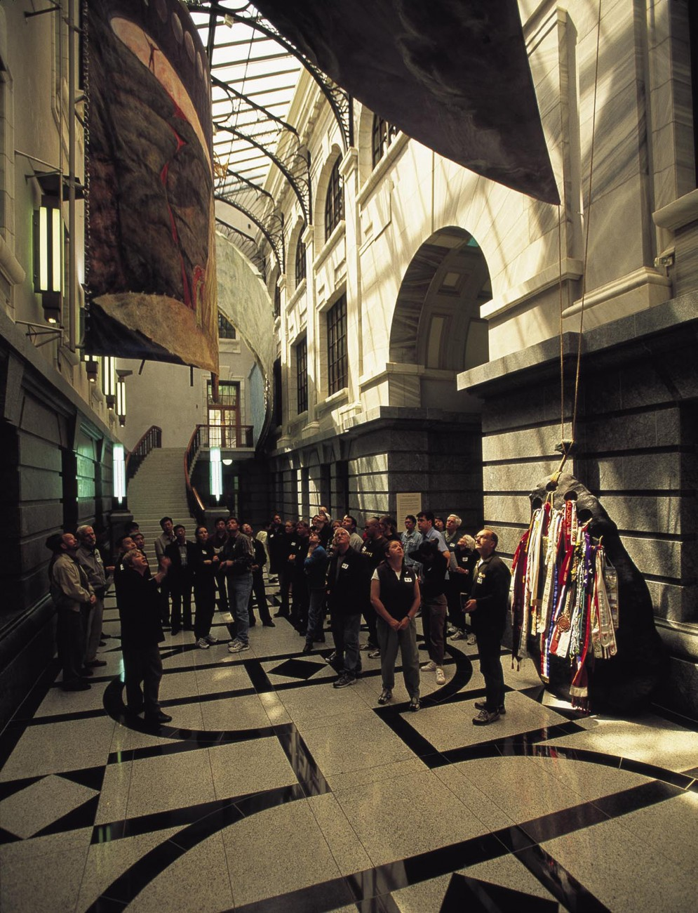 "Visitors crane their necks to take in the wonders of the Galleria, a newly enclosed space in Parliament House containing commissioned artworks, including Richard Parker's ribbon-bedecked ""Mooring Stone."""