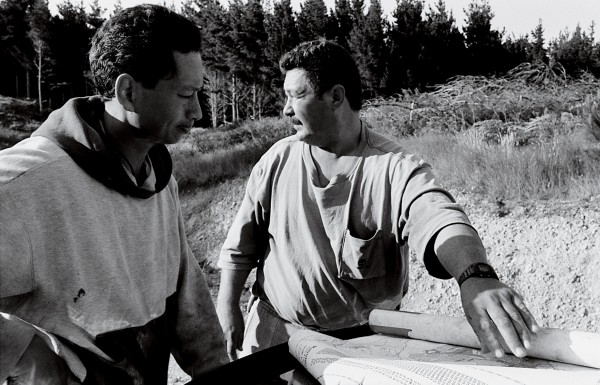 Cross-cutter Ian Black (above, left) consults a topographic map of the Manu Block with gang boss Howard Skipps to decide where he should fell next. At the other end of the process, a truckie tightens a safety chain on a load of logs marked for pulping and paper manufacture (below).