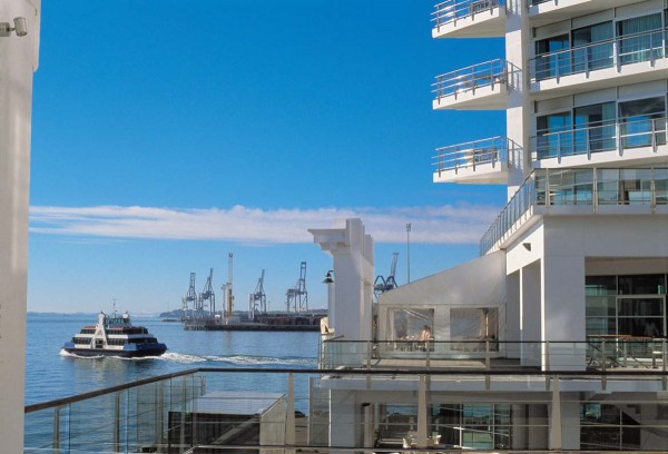 The swanky Hilton Hotel on Princes Wharf is a far cry from the gantries of the Bledisloe container terminal, visible against the sky. While the industrial arm of the port has gained in muscle at the eastern end of the wharf area, the western end has become gentrified. Here, ritzy apartments surround the Viaduct Harbour, and the passenger terminal shares a wharf with the Hilton.
