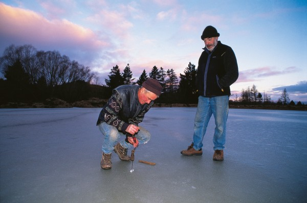 Ice master Merve Jamieson tests the ice thickness, watched by fellow curler Alan Dunford.