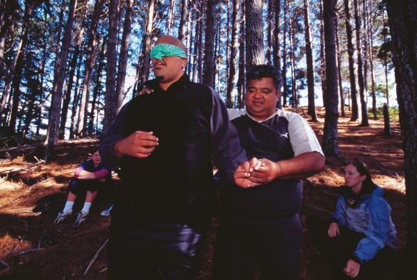 """Trees have a korero,"" says Howard Reti as he leads the blindfolded Tutavake Petero to greet a tree. After returning to the group, the blindfold is removed and Tutavake must find his tree among the maze of similar pines."