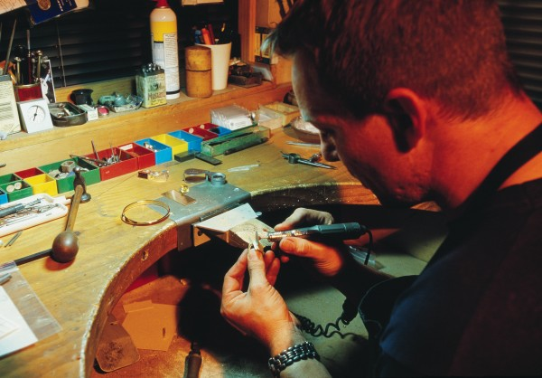Goldsmith Thorkild Hansen shapes a ring at his Nelson workshop. Since Jens Hansen's death in 1999, sons Halfdan and Thorkild have continued the family business. Most gold is used in jewellery. The metal's value is mainly driven by its scarcity—annual world production is only 2600 tonnes, and all the gold ever mined would make a cube about 19 m high.