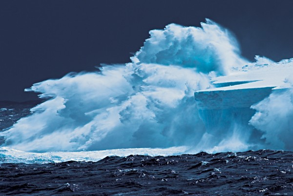 In the upper shot, a swell is breaking against an iceberg.