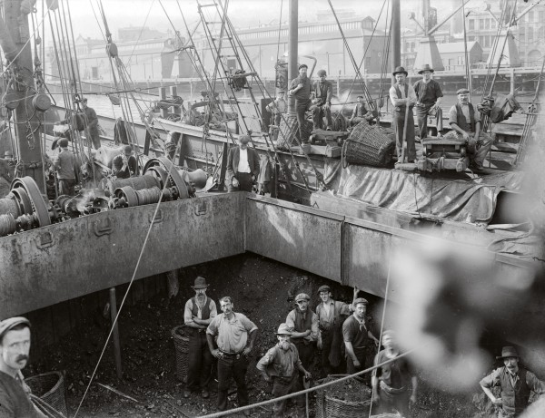 Work on the wharves was hard and most tasks were accomplished by manual labour. Frozen carcasses were lifted into slings and coal was shovelled into baskets (seen here) before derricks picked them up.