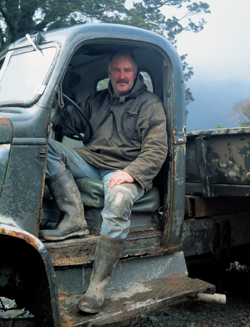 This West Coast truckie may not have a door to keep out the elements, but long gumboots and a parka certainly help.