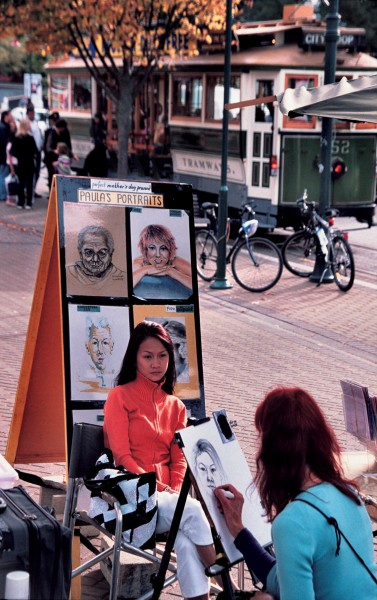 Boulevard artist Paula sketches during a weekend Arts Centre market. Many of the visitors to these markets—which offer quality craftwork—arrive on one of the city loop trams.