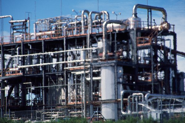 The Kaurex resin and wax extraction plant at Kaimaumau shimmers as solvent is burned off during its decommissioning in 1989. The plant was the most recent in a long line of attempts to extract kauri gum chips and dust from Northland's peat swamps.