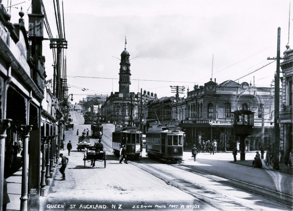 In 1922, the street was wide and pedestrians jay-walked with impunity. At this time, horse-power was still in common use, but trams-bot single and double-decker-and motor cars were rising in popularity. Turret at right of photograph is a tramway control box, and near the Town Hall the statue of Sir George Grey (since shifted to Albert Park) protrudes above a large palm.