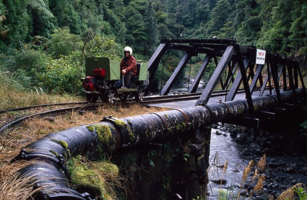 Wellington draws its water from rivers and reservoirs in the hills surrounding the city. At Wainuiomata, caretakers use a private railway to check a pipe that takes water from the Orongorongo River, through a three-kilometre tunnel and into a dam in the adjacent valley. Auckland's water also comes from a surface catchment, with reservoirs located in the Waitakere and Runua Ranges. In winter, excess water turns the spilllway of the Lower Nihotupu dam in Huia (one of the smaller reservoirs) into a bridal veil of cascading droplets.