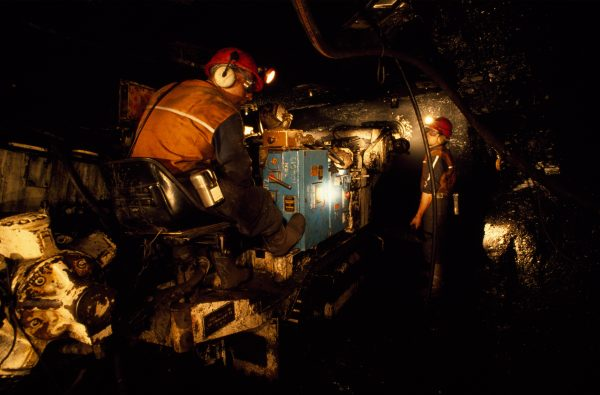 """Spike-studded spinning cone of a """"roadheader"""" mining machine burrows through rock in the new Strongman Number Two mine, wrenching a tonne of coal a minute from the face. With the help of machines like this, the mine's owners hope to extract 500,000 tonnes of coal each year for the next two decades."""
