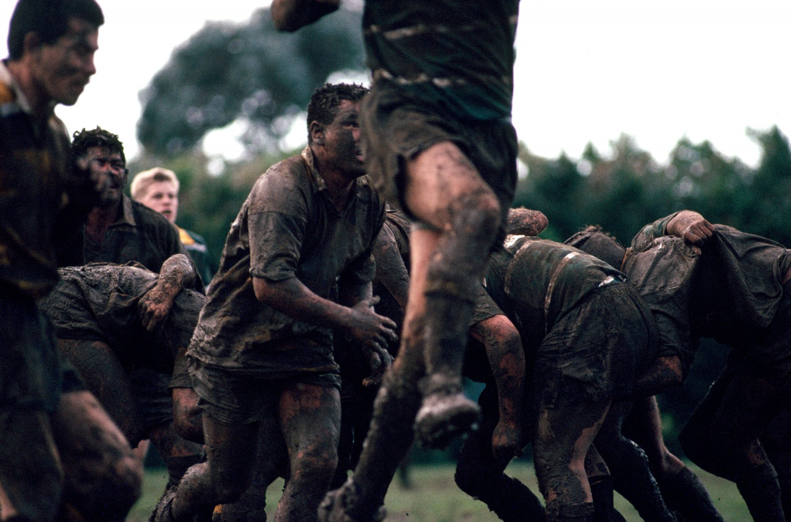 """Heavy"" conditions make mudbrothers of combatants Carlton and Eden as they labour at Cornwall Park, Auckland. Before the days of superior drainage, some fields were frequently inundated. One Otago winger was christened ""Speedboat"" after scoring a couple of tries at the ""deep end"" of Carisbrook Dunedin's premier rugby ground, in a particularly damp match against Poverty Bay in 1948."