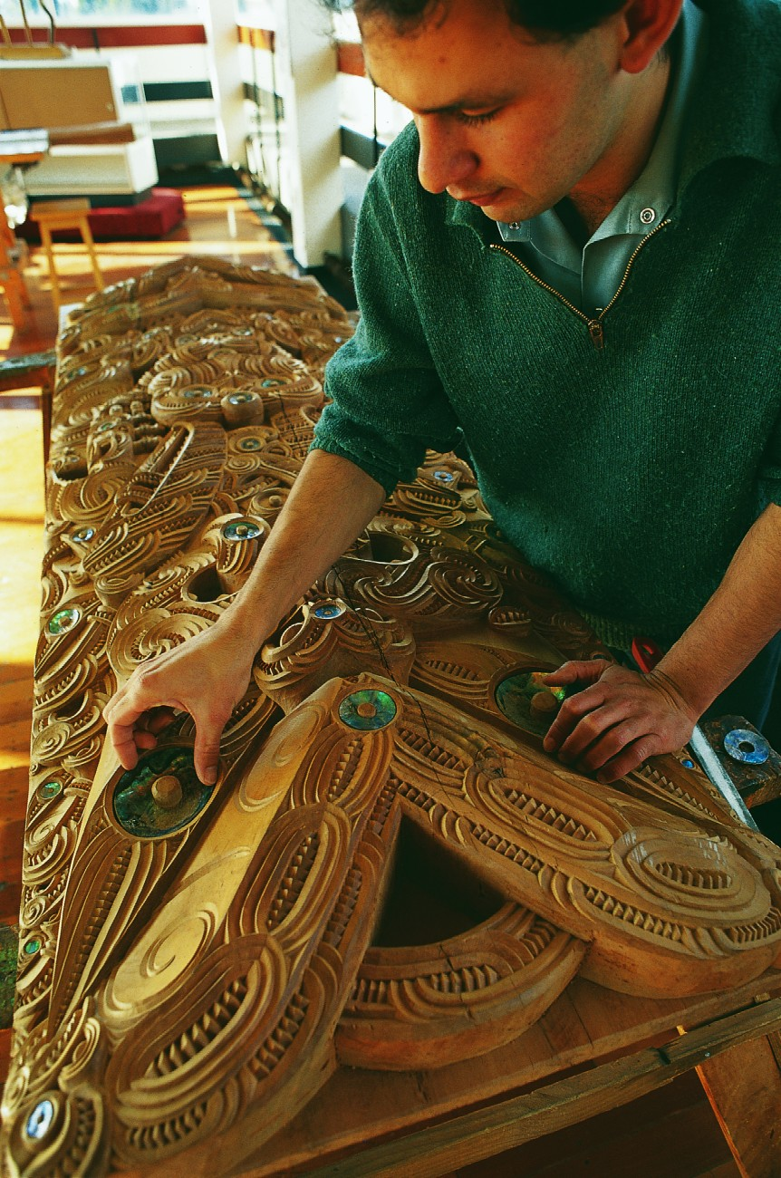 Maori have long valued the flash of paua shell to emphasise the life of carved ancestors in the gloom of the meeting house. Here Nathan Foote, a trainee carver at the NZ Maori Arts and Crafts Institute in Rotorua, checks fits the eye to his masterpiece.