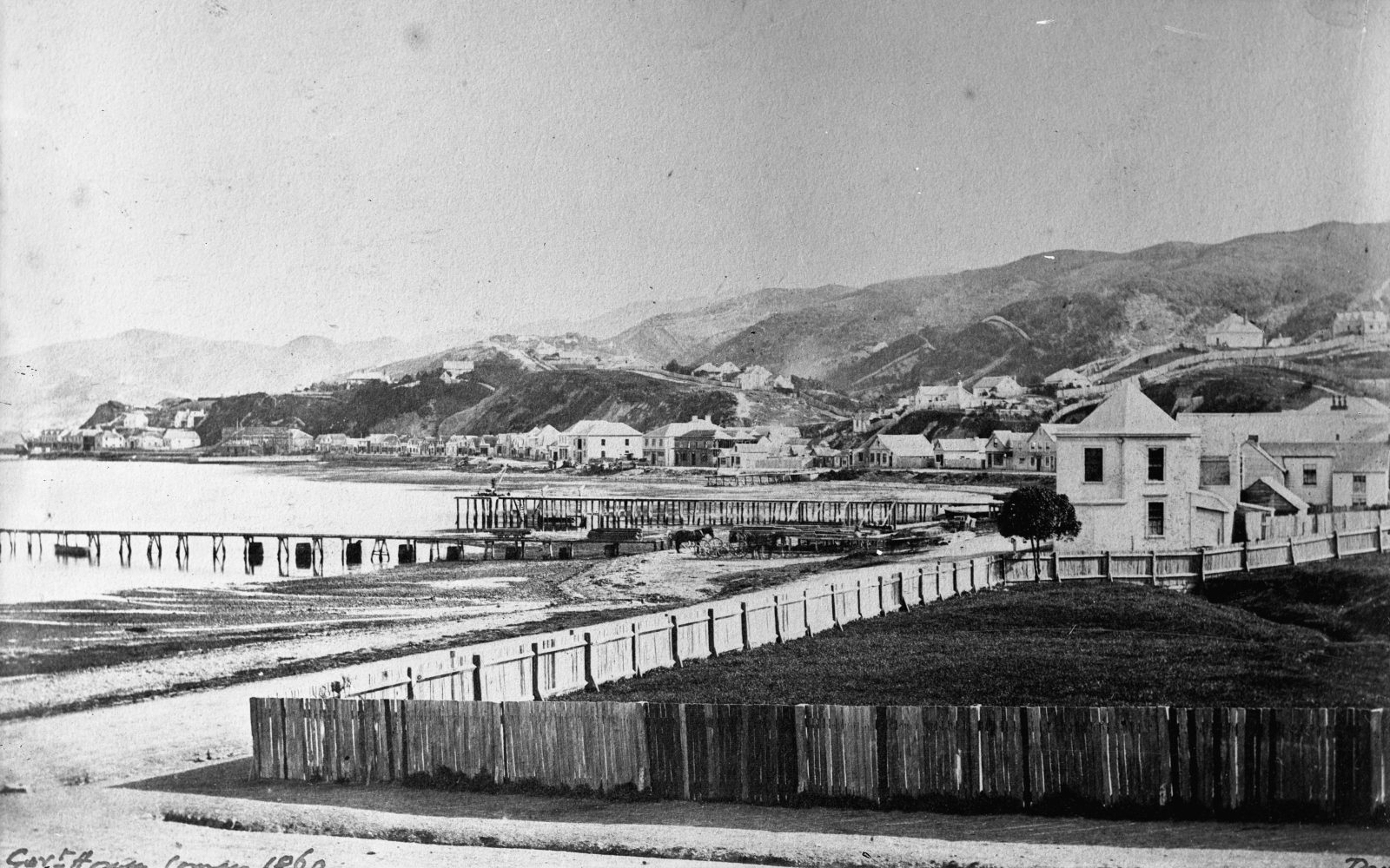 In Wellington Harbour, the 1855 earthquake raised the seabed by about a metre-and-a-half, making existing jetties useless. By 1860 when this photograph looking south along Lambton Quay was taken, the damage to buildings caused by the earthquake had long since been repaired, but the jetties seem to have been little modified.