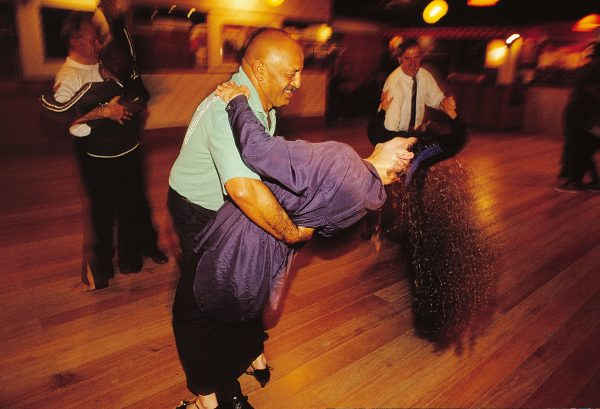 """Ballroom, Latin, rock'n'roll—all styles are served at the Albert School of Dancing. Located above a tyre service centre in Papatoetoe, the studio also appeals across the ethnic spectrum, with Europeans, Maori, Polynesians and Asians all keen to trip the light fantastic. """"Many people have met their future spouses at our classes,"""" says Albert Snelgar (background, right), here teaching the lambada. """"Others have made lasting friendships."""""""