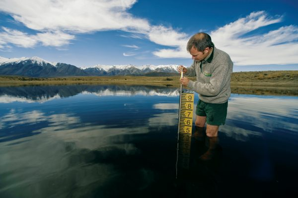 Department of Conservation ecologist Kennedy Lange checks the water level of a kettlehole near Lake Heron in the Ashburton Lakes basin. Kettleholes—sinks left behind by melting glacial ice—are home to resilient communities of animals and plants that must cope with haphazard extremes of inundation and dessication.