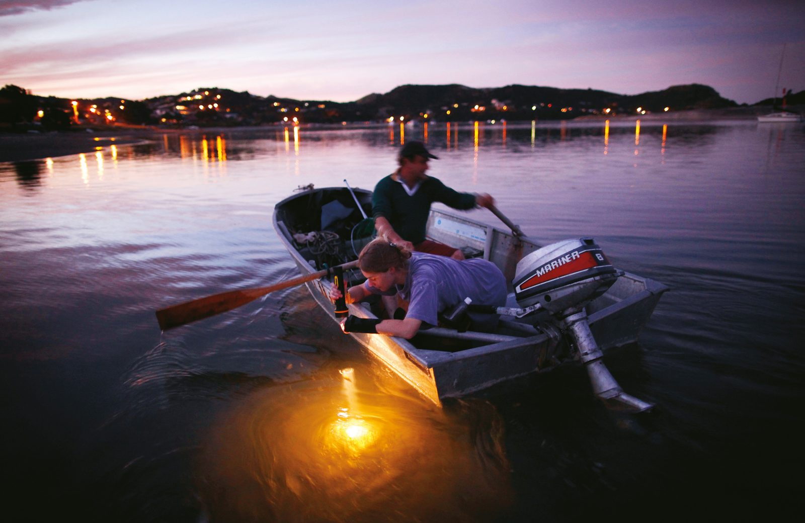 Rachel Lowrie peers into the Mangawhai estuary as her stepfather Michael Brown rows towards the township after their outboard motor broke down at the end of a day's fishing.